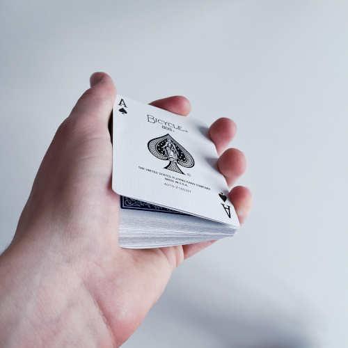 Daumen hält Karten davon ab, auf dem restlichen Stapel aufzuliegen