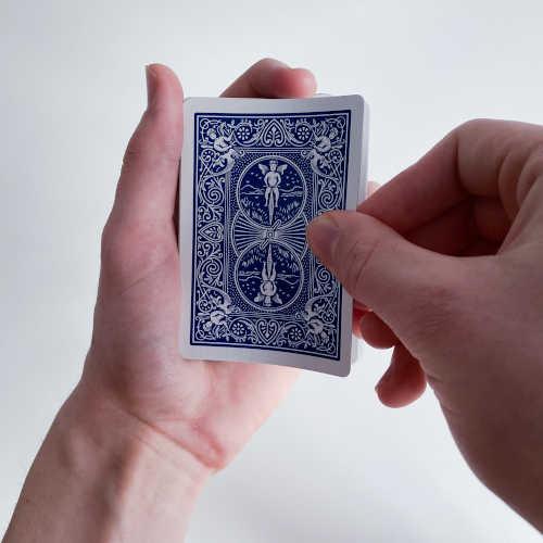 Karten werden mit Daumen, Zeige und Mittelfinger genommen