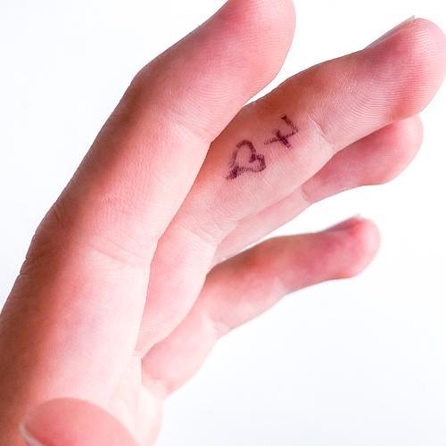aufgemalte Herz 7 auf dem Mittelfinger